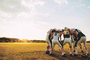 american-football-players-in-a-huddle-during-pract-SRX97E2-scaled