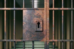 Prison interior. Locked rusty door closeup, dark background. 3d illustration