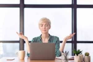 peaceful-businesswoman-relaxing-meditating-sitting-HBTZH7J-min-scaled