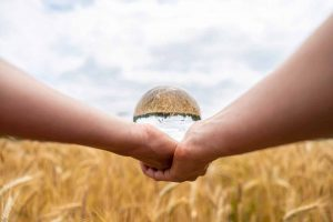 woman-holding-a-crystal-ball-over-wheat-field-3XKD2T8-scaled